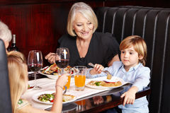 Grandparents with grandchildren. Smiling grandparents eating out with their grandchildren in a restaurant royalty free stock image