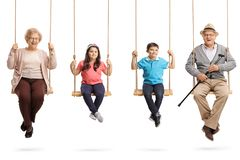 Grandparents and grandchildren on swings smiling at the camera. Full length portrait of grandparents and grandchildren on swings smiling at the camera isolated stock image