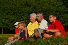 Grandparents and grandchildren together. Retired couple sitting, talking and relaxing together with their grandchildren Royalty Free Stock Image