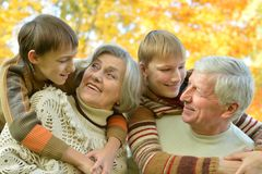 Grandparents and grandchildren. Together in autumn park royalty free stock image