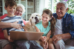 Grandparents and grandchildren using laptop in living room Stock Photography