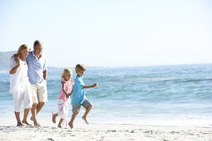 Grandparents and Grandchildren Walking Along Beach Stock Photography