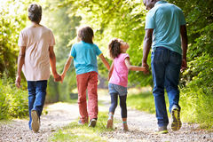 Grandparents With Grandchildren Walking Through Countryside. Looking At Each Other Whilst Holding Hands Royalty Free Stock Photography