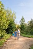 Grandparents and grandchildren walking outdoors. Back view of grandparents and grandchildren walking on a nature path stock photo