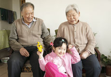 Grandparents with granddaughter. Asian grandparents with granddaughter at home royalty free stock photography