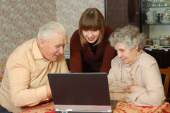 Grandparents and granddaughter. Looking to the laptop Royalty Free Stock Images