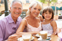 Grandparents With Granddaughter In Cafe. Grandparents With Granddaughter Enjoying Coffee And Cake In Caf Royalty Free Stock Images