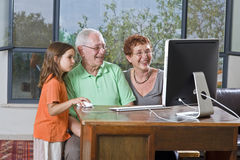 Grandparents and granddaughter with computer. At home Stock Images