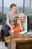 Grandparents and granddaughter with computer. At home Royalty Free Stock Photography
