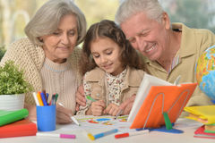 Grandparents with granddaughter drawing Royalty Free Stock Photography