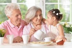 Grandparents with granddaughter drinking tea. At home stock image