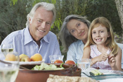 Grandparents With Granddaughter At Outdoor Table Royalty Free Stock Photography