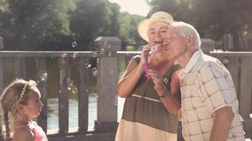 Grandparents and granddaughter outdoors. Senior man blowing soap bubbles, slow motion. Warm family relationship stock video