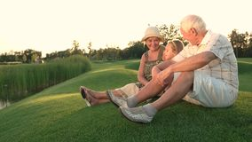 Grandparents and granddaughter outdoors. Senior man and woman sitting with grandchild on green hill and talking. Pass on life experience stock footage