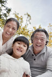 Grandparents and granddaughter in park Stock Photography