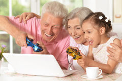 Grandparents and granddaughter playing computer game. Portrait of happy grandparents and granddaughter playing computer game on a laptop Royalty Free Stock Photo