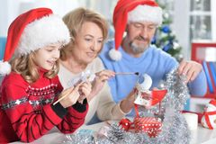 Grandparents with granddaughter preparing for Christmas. Portrait of grandparents with granddaughter in Santa hats preparing for Christmas at home Stock Photos