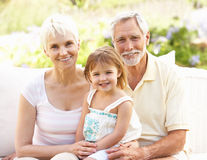 Grandparents And Granddaughter Relaxing In Garden Stock Photos