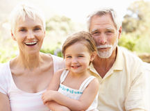 Grandparents And Granddaughter Relaxing In Garden. Smiling Royalty Free Stock Photos