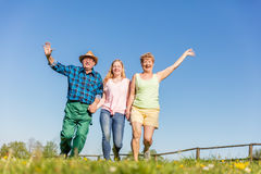Grandparents with granddaughter running happy on the field. Grandparents with granddaughter running together and waving in the countryside. Happy family time Royalty Free Stock Photos