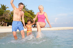 Grandparents With Granddaughter Splashing In Sea On Beach Stock Image