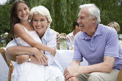 Grandparents With Granddaughter At Table In Garden Stock Photography