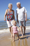 Grandparents And Granddaughter Walking Along Beach Royalty Free Stock Photography