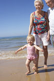 Grandparents And Granddaughter Walking Along Beach Stock Images