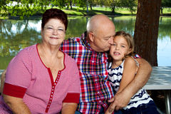 Grandparents Grandddaughter. A senior couple sits with their granddaughter. Grandpa gives his granddaughter a kiss while Grandma looks at the camera and smiles Royalty Free Stock Images