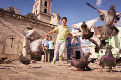 Grandparents And Grandson Boy Chasing Pigeons Flying. Happy tourist on holidays during vacation trip. Hispanic people traveling in Havana, Cuba. Grandpa and royalty free stock photos