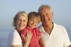 Grandparents With Grandson Enjoying Beach Holiday Stock Photos