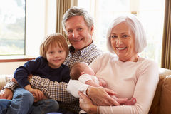 Grandparents With Grandson And Newborn Baby Granddaughter Stock Image