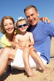 Grandparents And Grandson Sitting On Beach Royalty Free Stock Images