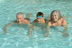 Grandparents with grandson in swimming pool. Smiling and posing Stock Photos