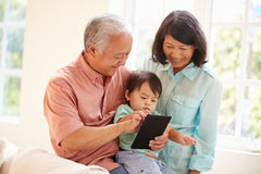 Grandparents And Grandson Using Digital Tablet Together Royalty Free Stock Photo