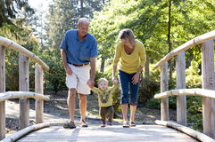 Grandparents and grandson walking on a bridge Stock Photo