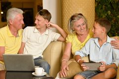 Grandparents and grandsons with digital devices. Grandparents and grandsons sitting on armchairs with digital devices Stock Photos