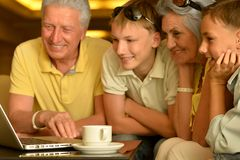 Grandparents and grandsons with laptop. Grandparents and grandsons sitting near table with modern laptop Royalty Free Stock Photos