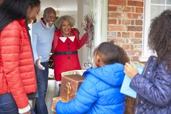 Grandparents Greeting Mother And Children As They Arrive For Visit On Christmas Day With Gifts royalty free stock photos