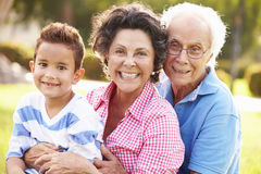 Grandparents Having Fun In Park With Grandson stock photo