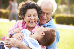 Grandparents Having Fun In Park With Grandson Stock Photography