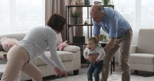 Grandparents enjoying with baby granddaughter at home. Grandparents having fun swinging baby granddaughter at home stock footage