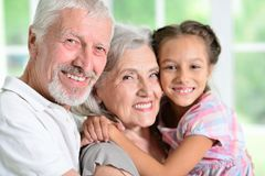 Grandparents with her granddaughter posing Stock Photo