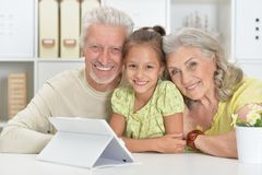 Grandparents with her granddaughter using laptop at home Royalty Free Stock Photos