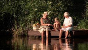 Grandparents and kid having fun outdoors. stock footage