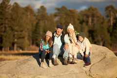 Grandparents and kids sitting on rocky outcrop near a forest Royalty Free Stock Photography