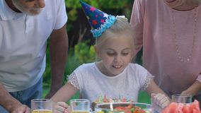 Grandparents kissing their beloved birthday granddaughter on cheeks, happiness. Stock footage stock video footage