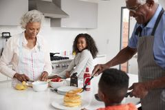Grandparents In Kitchen With Grandchildren Making Pancakes Together stock image