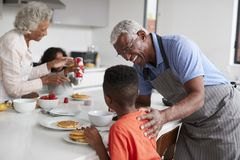 Grandparents In Kitchen With Grandchildren Making Pancakes Together stock photos