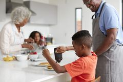 Grandparents In Kitchen With Grandchildren Making Pancakes Together stock photography